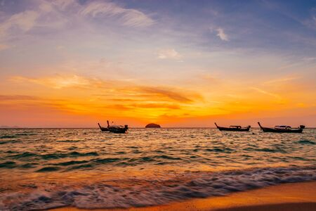 Spectacular orange marine sunset in Koh Lipe, Thailand reflecting over the surface of the ocean with scattered traditional wooden boats moored offshore Foto de archivo - 130712545