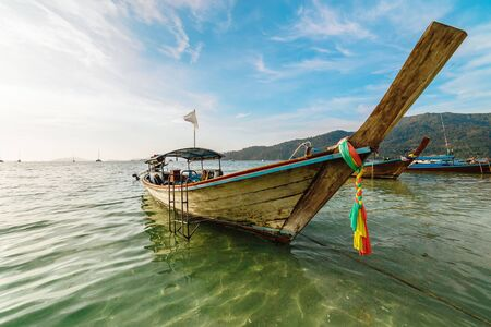 Traditional Thai wooden boat in Koh Lipe, Thailand with colorful textile tied around the high prow moored in shallow sunlit water offshore in a lagoon or sheltered bay in a summer travel concept Фото со стока