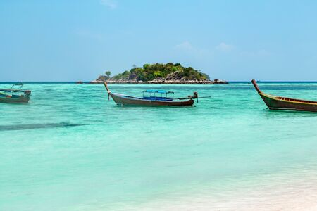 Traditional Thai wooden boat moored in a sheltered lagoon with crystal clear sparkling blue water with an offshore island in the background, Koh Lipe, Thailand