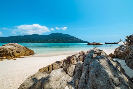 Deserted white sandy tropical beach with rock formations bordering an azure blue sea with distant island and moored boat in Koh Lipe, Thailand