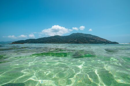Sparkling crystal clear pristine ocean on Koh Lipe, Thailand with a view over the water to an offshore island an idyllic getaway for a summer vacation Banque d'images - 130713019