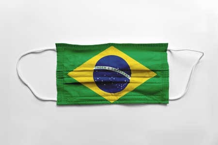 Face mask with Brazil flag printed, on white background, isolated.