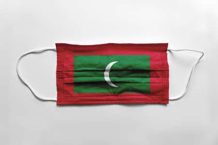 Face mask with Maldives flag printed, on white background, isolated.
