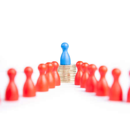 The concept of wage or pay gap: discrimination between men and women. Blue pawn representing men on top of coins. Stockfoto