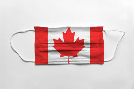Face mask with Canada flag printed, on white background, isolated.