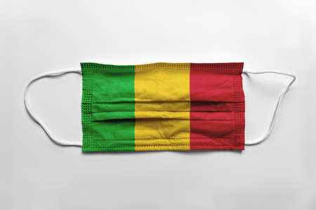 Face mask with Mali flag printed, on white background, isolated.