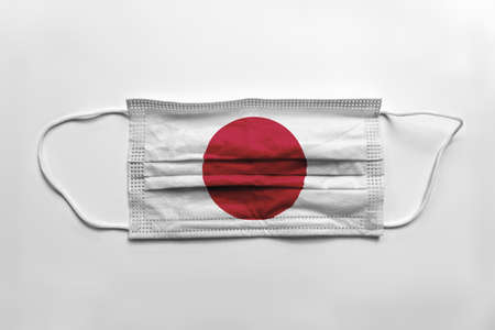 Face mask with Japan flag printed, on white background, isolated.