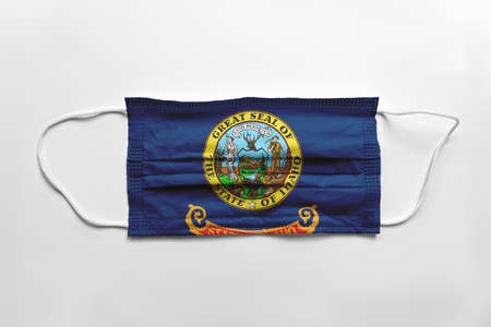 Face mask with Idaho flag printed, on white background, isolated safety concept