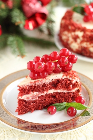 A piece of cake  red velvet  on the background of a pine branch