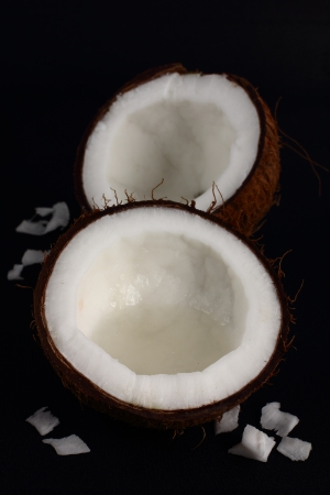 Halves of a coconut on a black background