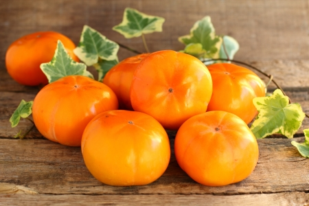 Persimmon fruit on the background of the grey boards  Stock Photo