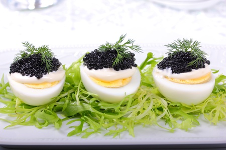 Appetizer of eggs with black caviar