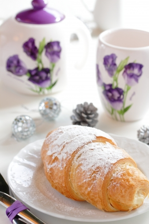 Croissant on the background of cups and a kettle  Stock Photo - 16672205