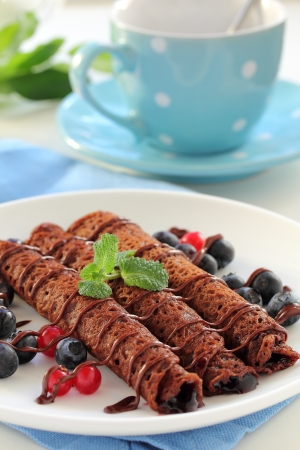Chocolate pancakes with blueberry sauce and berries   Stock Photo