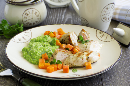Pieces of chicken with pea puree and pumpkin.