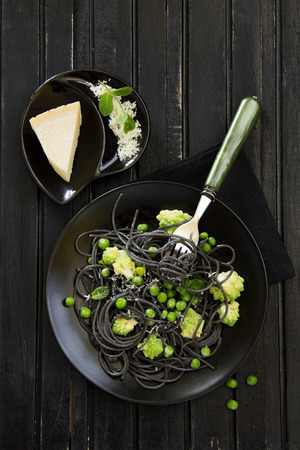 Cuttlefish ink spaghetti with broccoli and green peas. Stock Photo