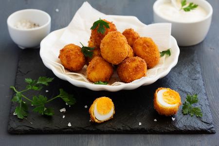 Quail eggs, deep fried with white sauce. Stock Photo