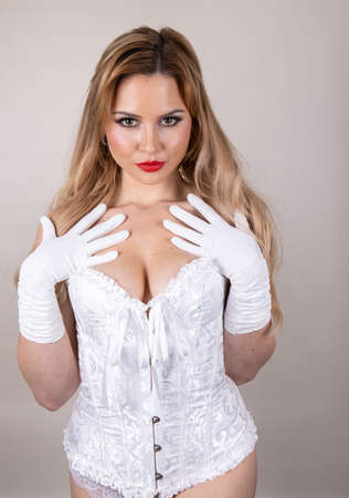An attractive woman with long blonde hair and red lipstick wearing a white corset looking and seductive.