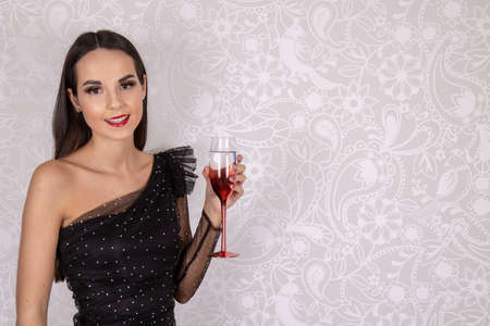 A sexy elegant attractive slim woman wearing a little black dress and stockings holding a glass of wine ready for a party, wedding or event