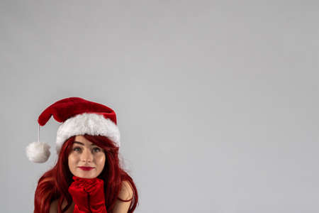 Young female attractive model with auburn hair and red lipstick sat down in a studio with a white background wearing a   santa outfit with a red Santa hat with red velvet gloves.