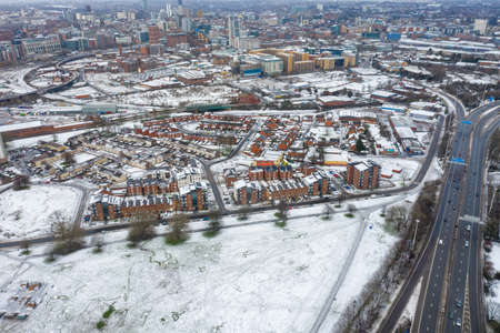 Aerial photo of a snowy day in the city of Leeds in the UK, showing rows of terrace houses with snow covered roofs in the Village of Beeston in the winter time Editöryel