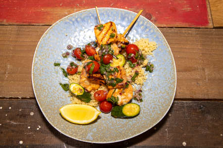 A delicious plate of Spring Salmon and Prawns Skewers with couscous salad and citrus salsa on a wooden kitchen table