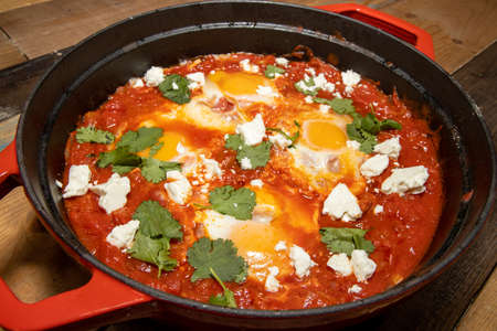 A delicious pot of Shakshuka with avocado and harissa eggs boiling in a large red cook pot