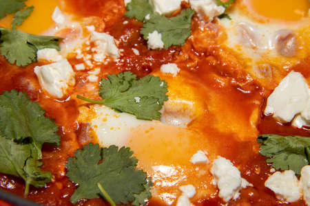 A delicious pot of Shakshuka with avocado and harissa eggs boiling in a large pan Stok Fotoğraf