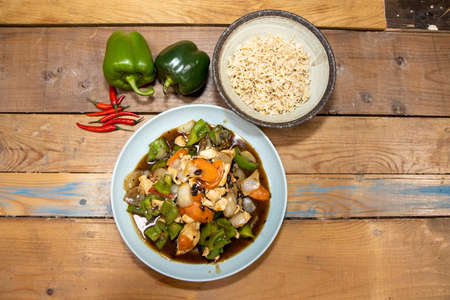 A delicious bowl of Chicken with Green pepper Stir Fry with white rice and peppers with chillies on a wooden kitchen table Stok Fotoğraf