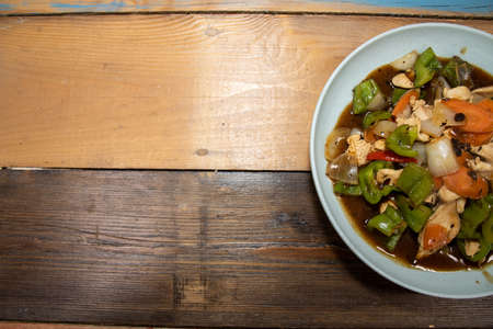 A delicious bowl of Chicken with Green pepper Stir Fry on a wooden kitchen table