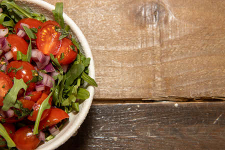 A bowl of tomatoes and herbs on a wooden table Stok Fotoğraf