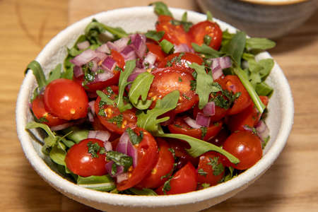 A bowl of tomatoes and herbs on a wooden table
