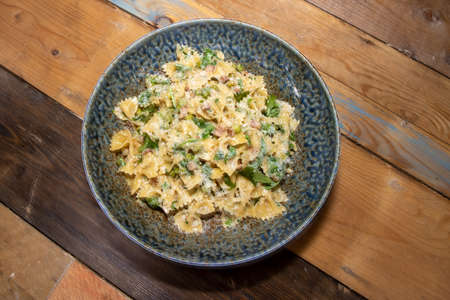 A delicious plate of Pancetta Parmesan and Pea Pasta on a wooden kitchen table