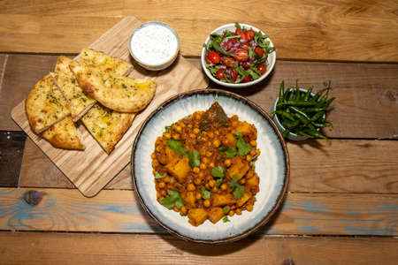 A bowl of the delicious Indian dish Chana Masala made from chickpeas and potatoes on a wooden kitchen table