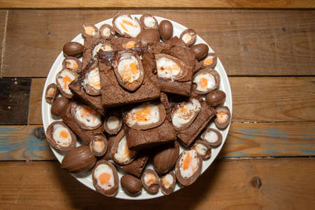 A plate of delicious chocolate cream easter egg brownies, chocolate easter eggs treats on a wooden kitchen table