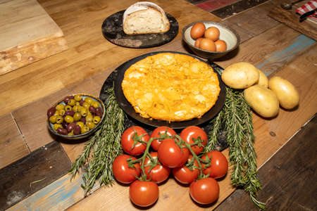 A delicious Spanish tortilla on a wooden kitchen table surrounded by the ingredients used to create the dish