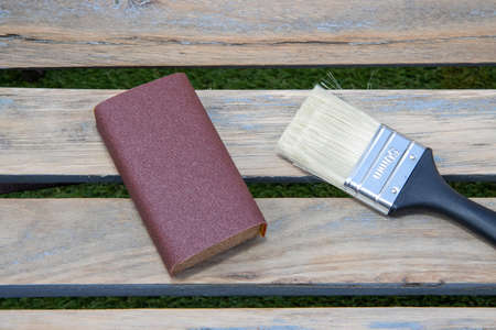 A sanding block and a paint brush on a wooden bench ready to sand down, home improvement woodworking concept
