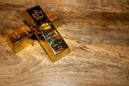 Two solid gold bars on a wooden table