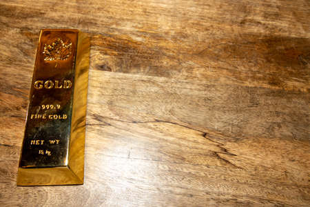 A solid gold bar on a wooden table