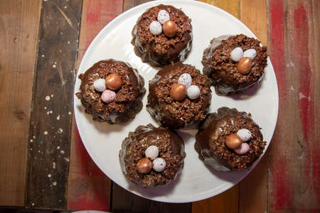 A selection of Easter Chocolate nest Cakes topped with three little chocolate mini eggs on a white plate Stok Fotoğraf