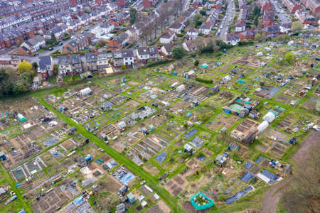 Aerial photo of a community garden allotment in the city of Leeds in the UK showing the community gardens alone side rows of residential houses taken in the string time