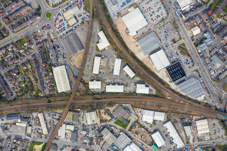 Top down aerial photo of the British town of Wakefield in West Yorkshire in the UK showing train tracks that are crossing taken in the spring time