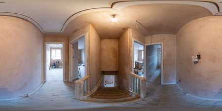 360 Degree panoramic sphere photo of construction work being done on an old British terrace house showing the hallway and main stairs with wooden floors in the house