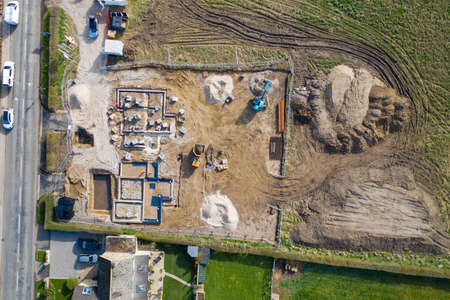 Aerial photo of the UK village of Wetherby in Yorkshire showing building work being done on a property in the village with the foundations of new houses being built in a field Stok Fotoğraf