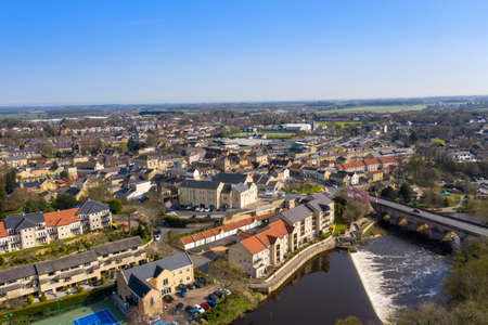 Aerial photo of the beautiful village of Wetherby, Leeds, West Yorkshire in the UK showing the main street along side the river and waterfall and the main bridge going into the town