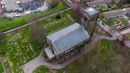 Aerial drone photo of a historical church in the British town of Alverthorpe in Wakefield in the UK know as St Paul's Church, showing the church and grave yard in the spring time