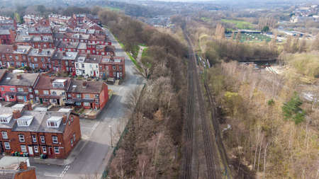 Aerial photo of the village of Kirkstall in the city of Leeds in the UK showing rows of terrace houses along side a train track in the spring time