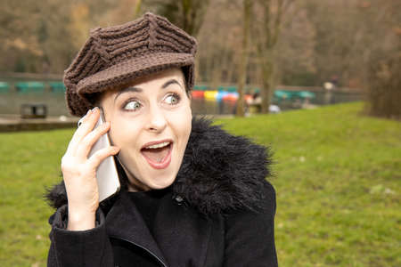 An attractive young woman in a public park on a cold day in the winter time on the phone looking happy and excited Stok Fotoğraf