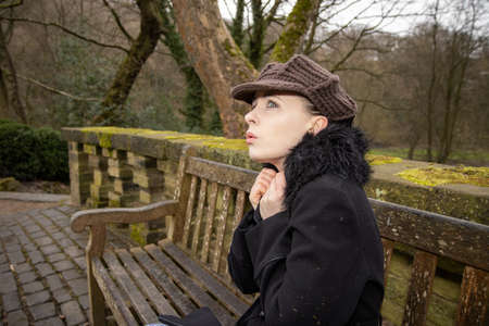 A attractive young woman in a public park sat on an old bench on a cold day in the winter time looking upset and scared Stok Fotoğraf