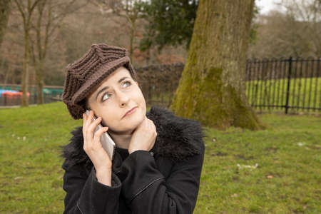 An attractive young woman in a public park on a cold day in the winter time on the phone looking up as if she is thinking